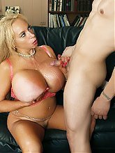 Echo Valley holds on to her pair of enormous breasts while she gets screwed on the couch